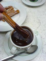 Churro eingetunkt in heißer Schokolade