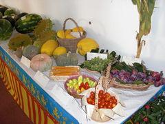 Tisch mit Gemüse, Weintrauben, Obst und Sonnenblumen