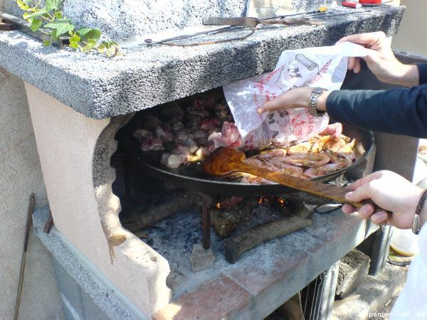 Hinzufügen von Fleisch in die Paella