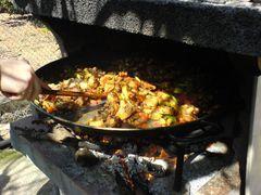 Hinzufügen von Tomaten und Paprika zur Paella