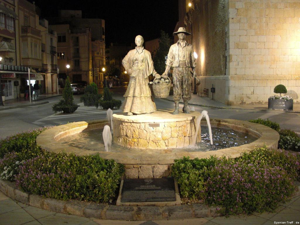 Brunnen mit zwei Figuren die einenKorb voller Artischocken halten