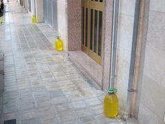 Flaschen mit gelber Flüssigkeit an Häusern gegen Hundeurin
