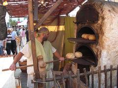 Bäcker schiebt auf dem Markt, Brot in den Ofen.