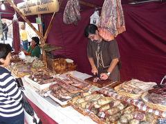 Wurstwaren am Marktstand und Mann in altertümlicher Kleidung
