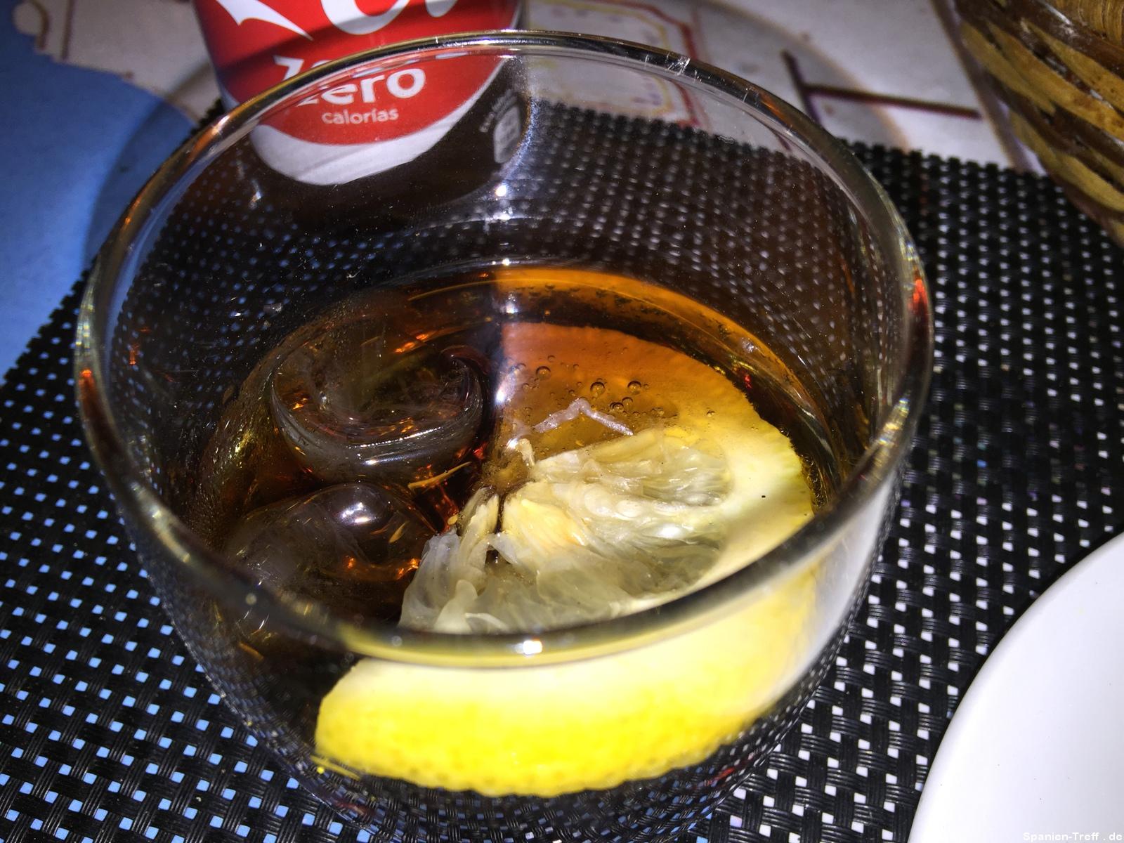 Coca Cola mit Eiswürfeln und Zitronenscheibe